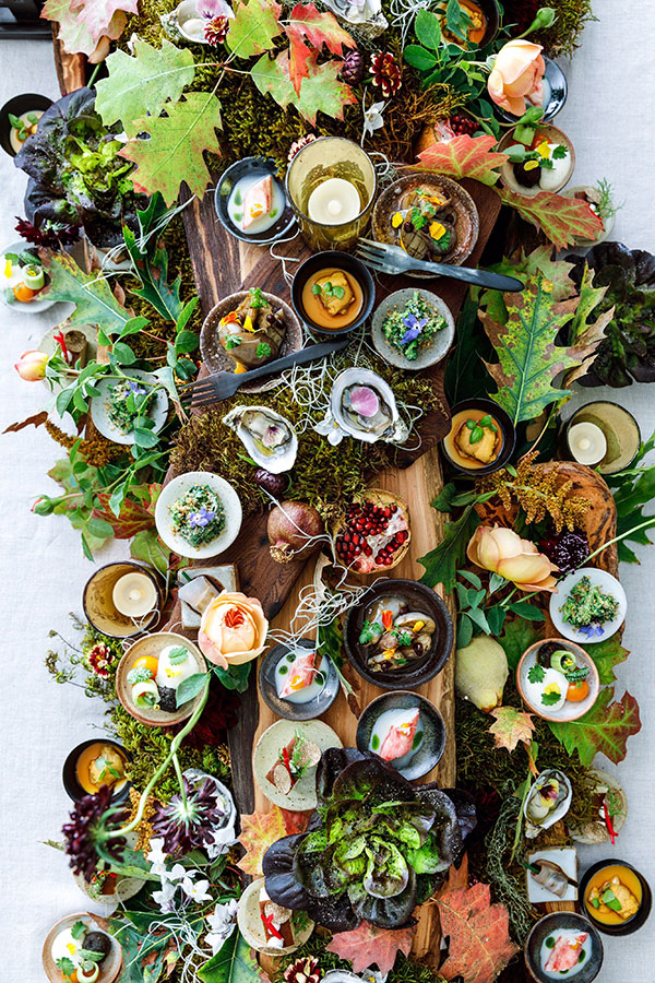 A large table setting with an array of colorful dishes of food surrounded by decorative leaves, flowers, and moss.